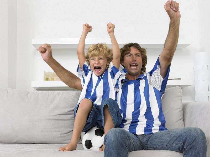Папа и сын вместе радуются выигрышу футбольной команды