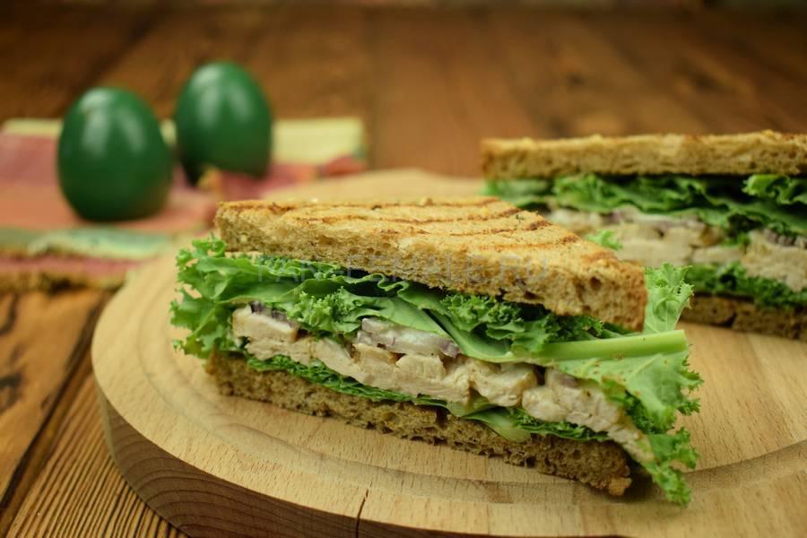Сэндвич на основе зернового хлеба с индейкой, красным луком, кудрявой капустой